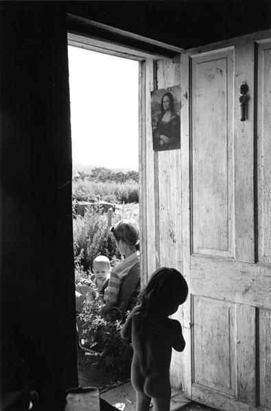 Mother and babies thru adobe doorway, El Rito