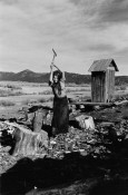 Woman chopping wood. In Shelter Book.